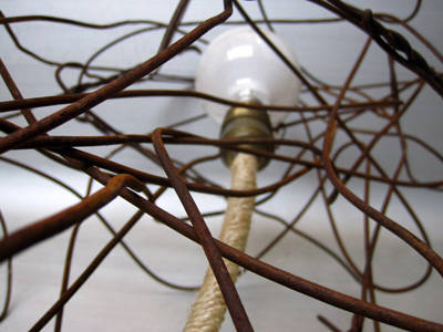This lamp consists of a tangle of rusty wire, suspended from the top with the light fixture wire wrapped in hemp rope